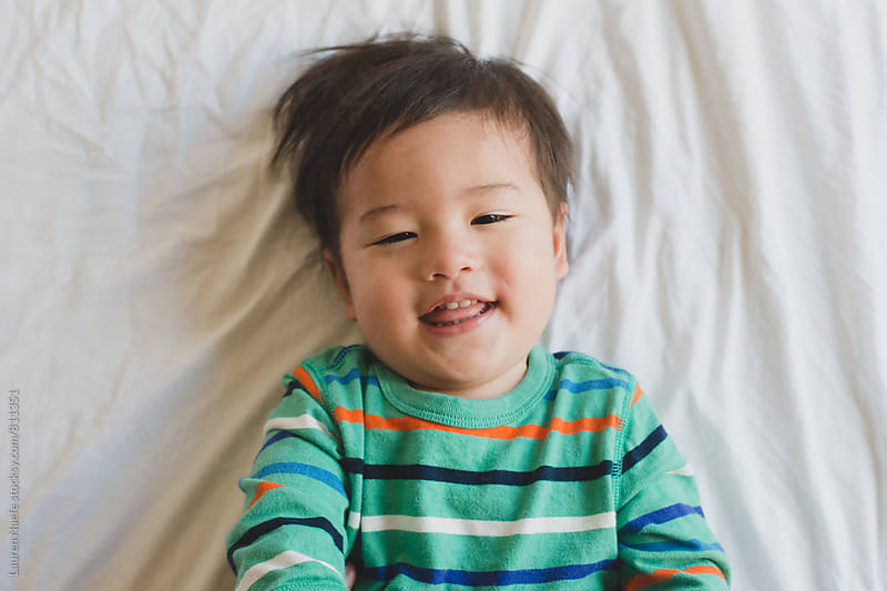 Happy toddler smiling at camera by Lauren Naefe for Stocksy United