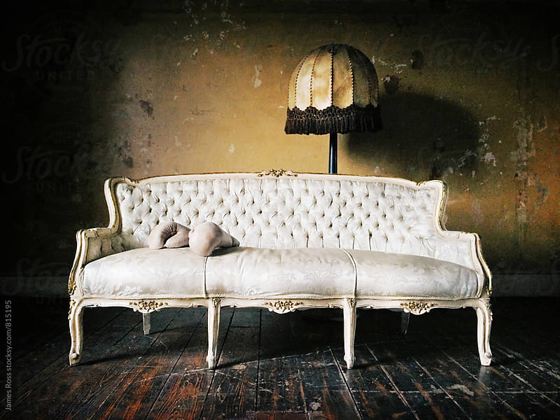 A chaise longue with boxing gloves and lamp stand by James Ross for Stocksy United
