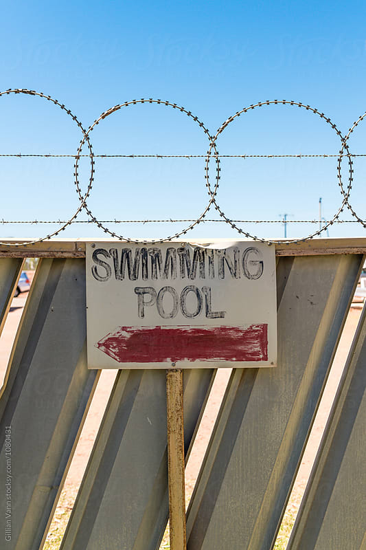 old sign for a swimming pool, with barbed wire above by Gillian Vann for Stocksy United