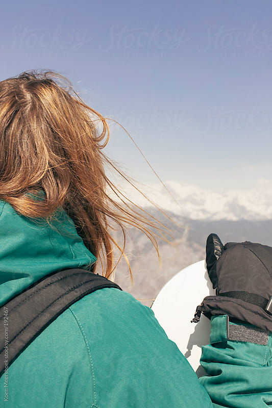 Woman holding her snowboard while looking to the mountains. by Koen Meershoek for Stocksy United