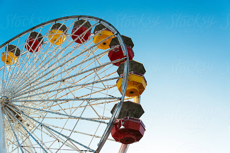 Detail of colourful ferriss wheel against blue sky by Alejandro Moreno de Carlos for Stocksy United