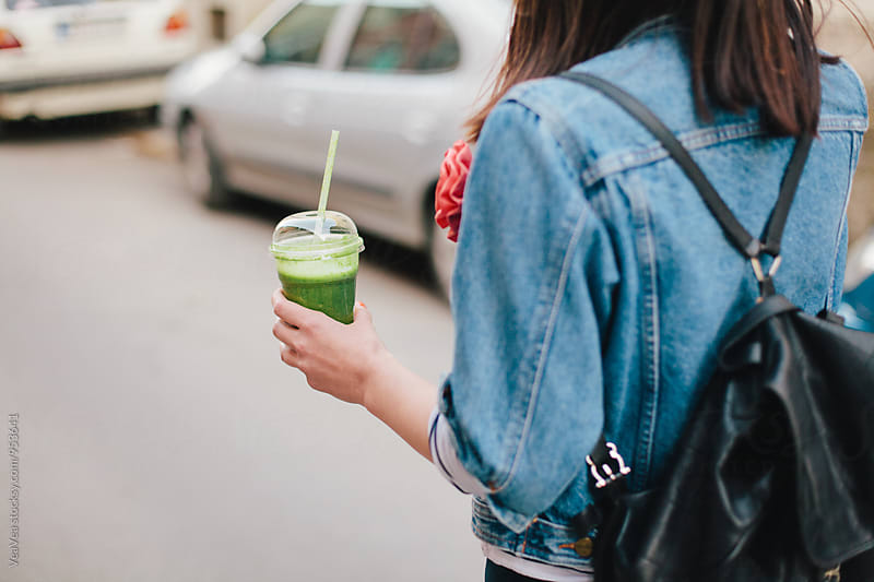 Stylish woman drinking a smoothie in the street by Marija Mandic for Stocksy United