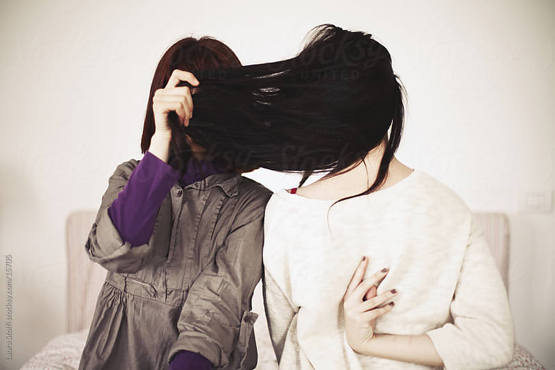 Two girls, one hiding her face with hair, the other seen from the back while sitting on bed by Laura Stolfi for Stocksy United