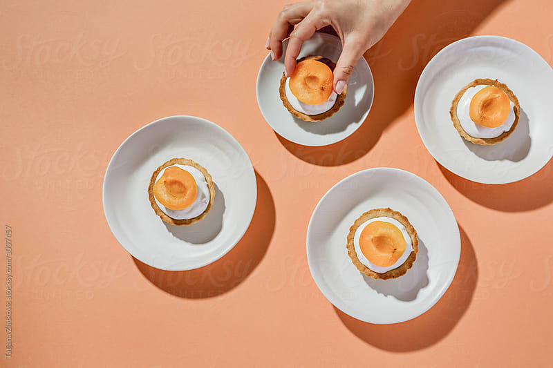 Hand is putting apricot on vegan tart by Tatjana Ristanic for Stocksy United