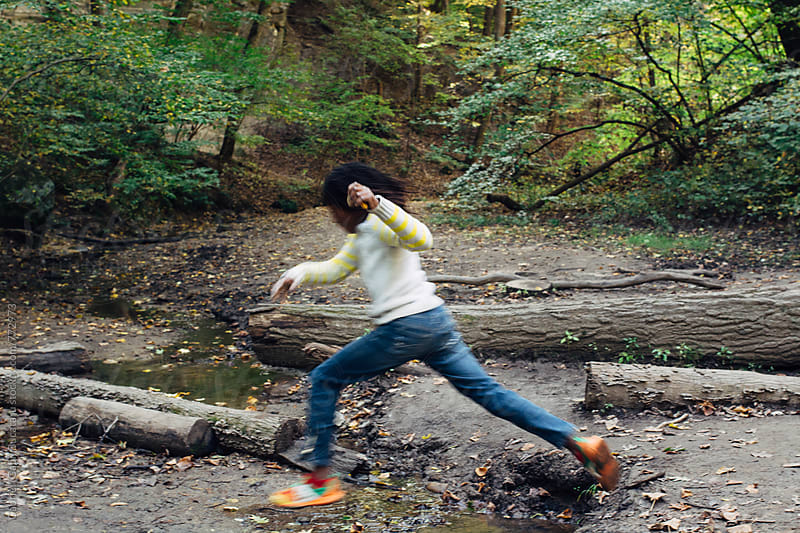 Black girl jumping over a creek in a forest by Gabriel (Gabi) Bucataru for Stocksy United