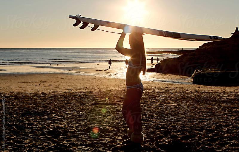 Girl in bikini walking beach with surfboard on her head, sun flare behind by Monica Murphy for Stocksy United