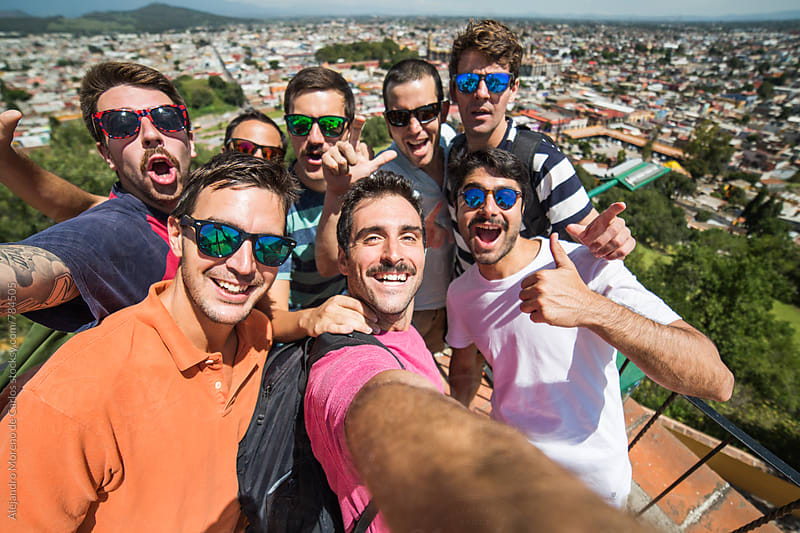 Group of young men selfie portrait from a lookout with views of the city behind by Alejandro Moreno de Carlos for Stocksy United
