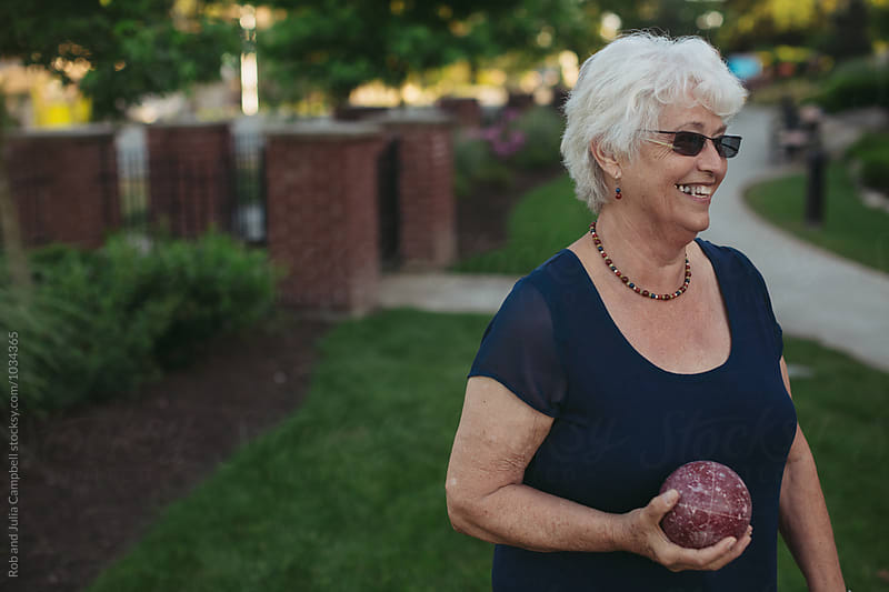 Healthy caucasian senior woman playing fun game of bocce ball outside by Rob and Julia Campbell for Stocksy United