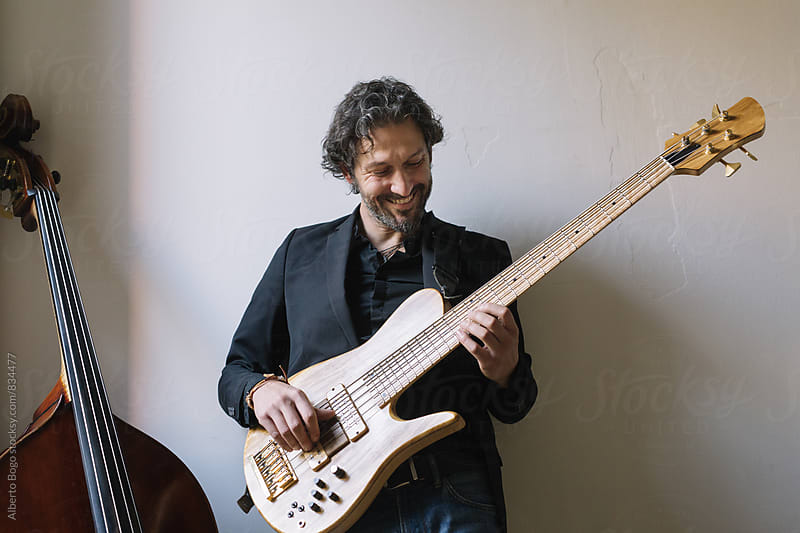 Male musician playing an electric bass guitar  by Alberto Bogo for Stocksy United