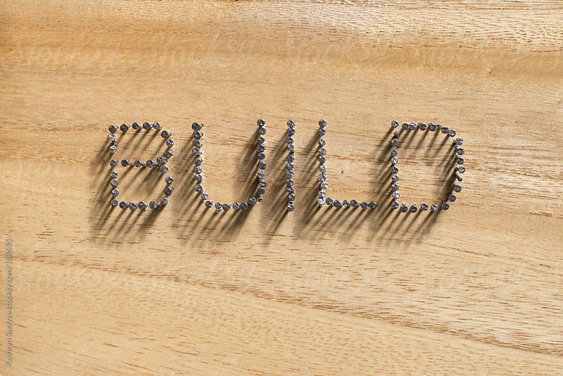 Build is spelled out with nails against a wooden background by Kathryn Swayze for Stocksy United