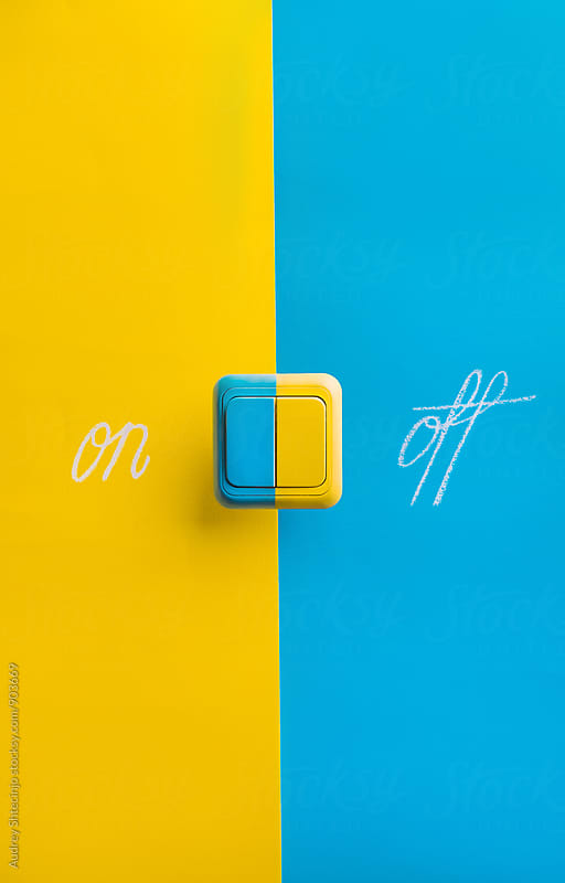 Switch for turning light or device ON or OFF on yellow and blue background. by Marko Milanovic for Stocksy United