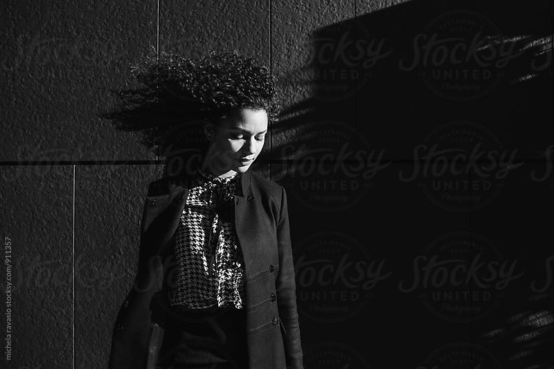 Elegant young woman with her face turned down and the wind tousled hair by michela ravasio for Stocksy United
