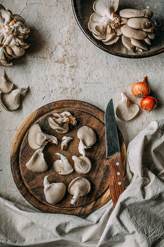Close-up of mushrooms on wooden board with knife by Marija Savic for Stocksy United