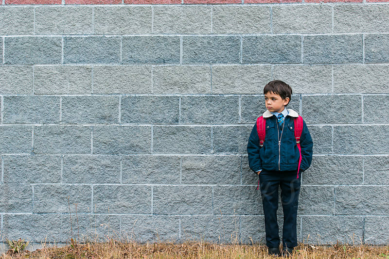 young boy stands cautiously outside a school wall by Tara Romasanta for Stocksy United