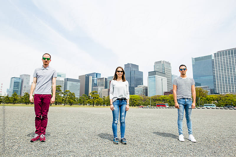 Portrait of friends standing in front of a Tokyo skyline. by BONNINSTUDIO for Stocksy United