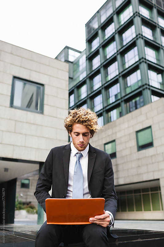 Young businessman using his laptop out of the office by michela ravasio for Stocksy United