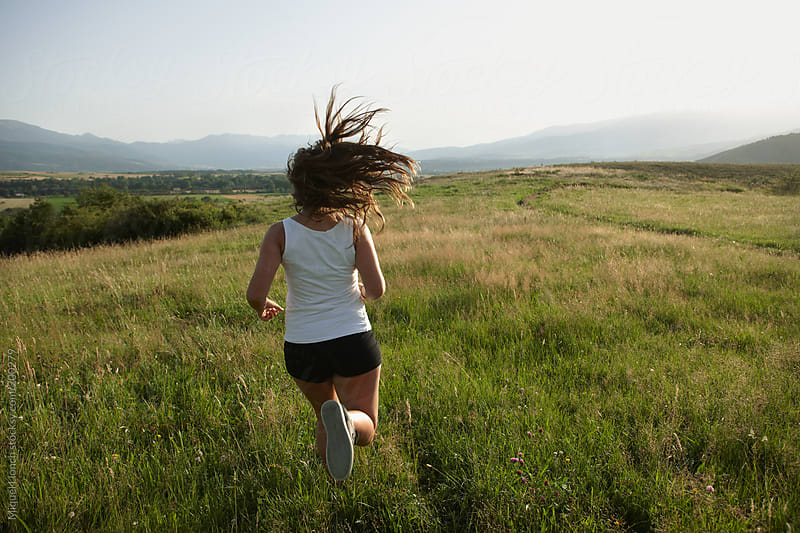 Young girl with long hair motion running through the fields by Miquel Llonch for Stocksy United