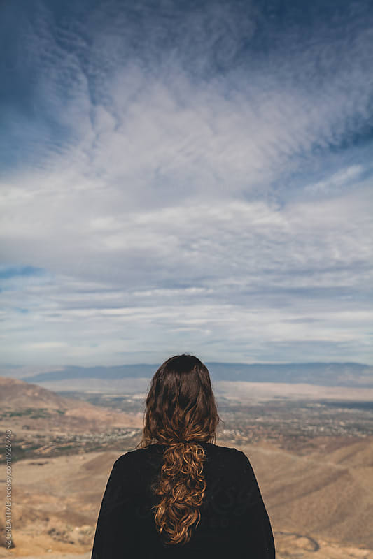 Woman looking out at desert landscape in California. by Robert Zaleski for Stocksy United