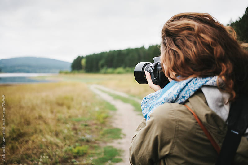 Young woman taking pictures in the mountain with dslr camera by Aleksandar Novoselski for Stocksy United