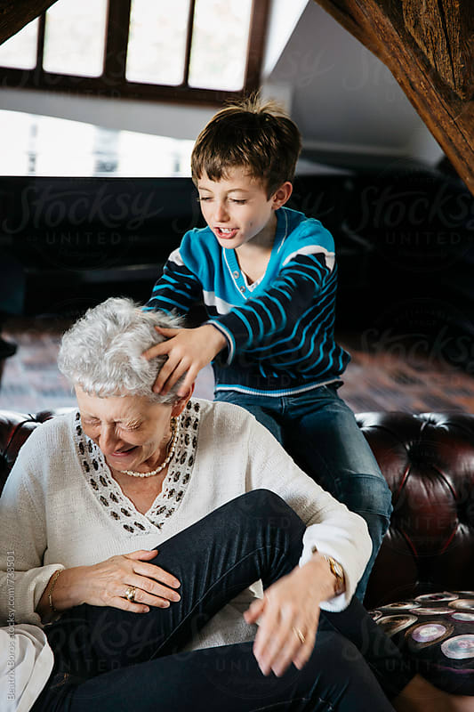 Naughty grandson playing with grandma, who is laughing with an expression on her face by Beatrix Boros for Stocksy United