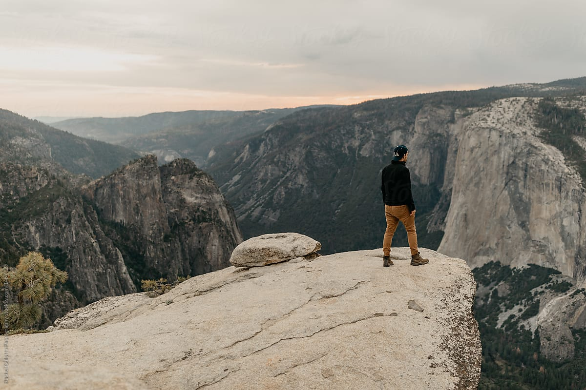 Man Standing at The Edge of A Mountain Cliff in Yosemite by