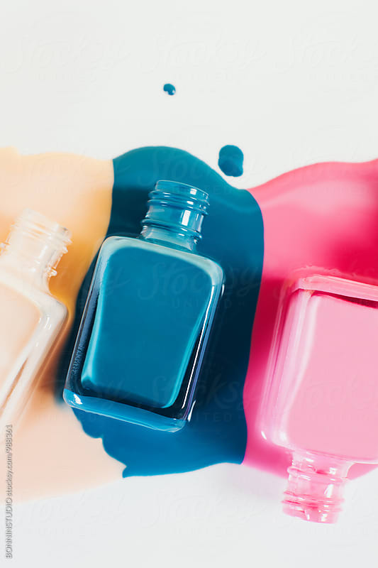 Nail polish bottles in puddles of nail polish liquid. by BONNINSTUDIO for Stocksy United
