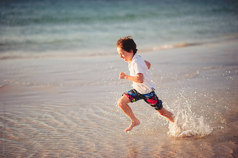 Boy running through water at the beach by Angela Lumsden for Stocksy United