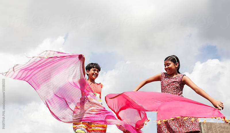 Two teenage girls playing and making fun by PARTHA PAL for Stocksy United
