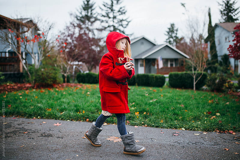 Little Girl in Red Coat Walks Briskly Down Her Driveway by Amanda Voelker for Stocksy United
