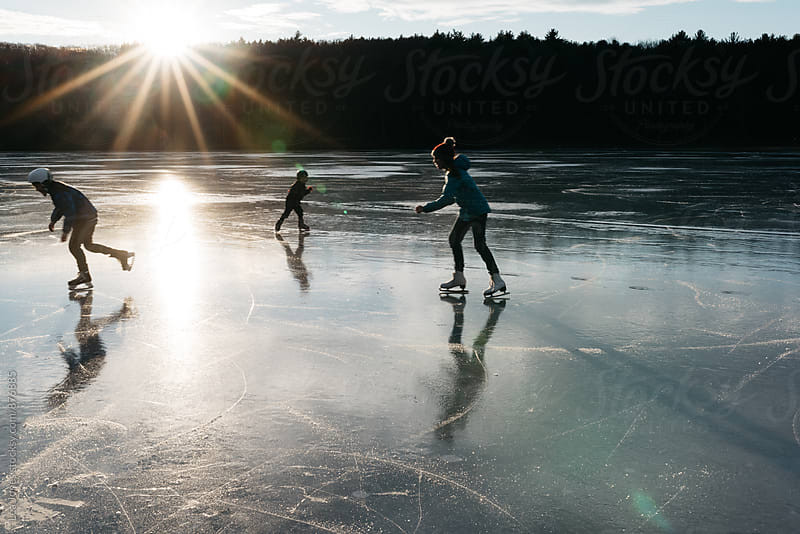 three kids skating on lake with sunset by Léa Jones for Stocksy United