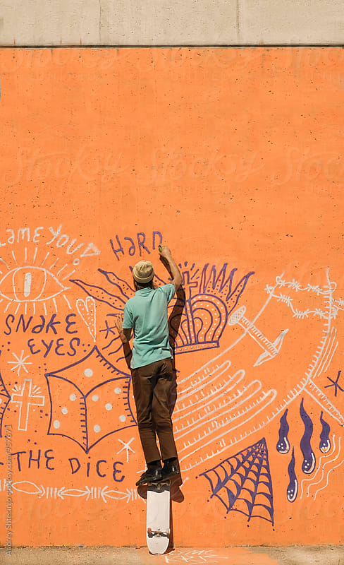 Young hip man in cool outfit  writting graffiti on orange .wall  on street. by Marko Milanovic for Stocksy United