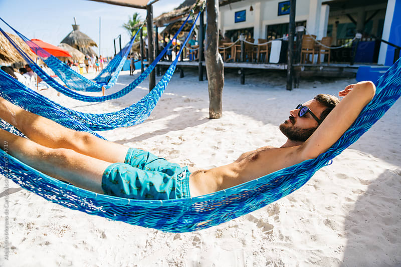 Young man resting on a hammock in a tropical beach bar by Alejandro Moreno de Carlos for Stocksy United