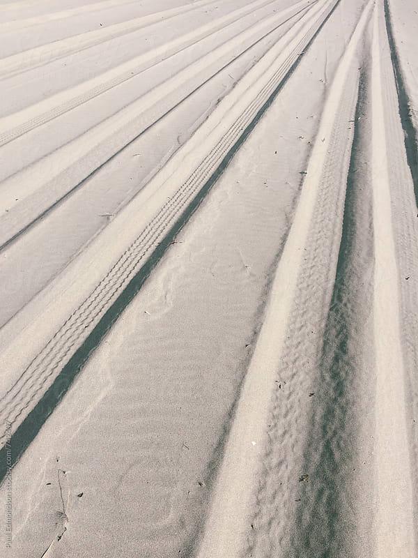 Tire tracks on beach by Paul Edmondson for Stocksy United