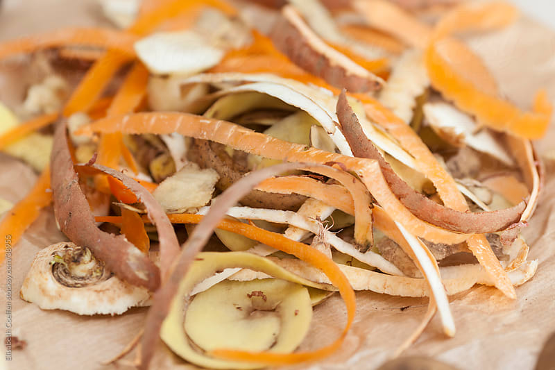 Peelings of root vegetables on parchment paper with a knife by Elisabeth Coelfen for Stocksy United