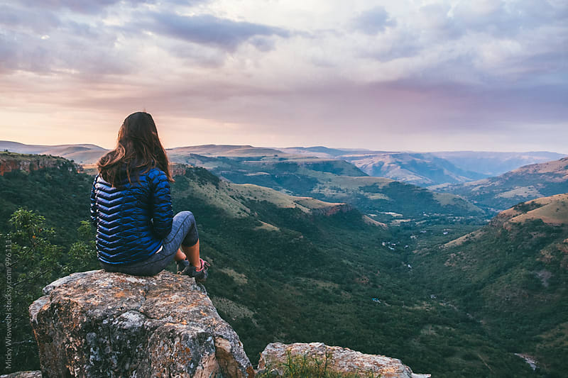 Hiker resting on a rocky outcrop overlooking a scenic valley at sunset by Micky Wiswedel for Stocksy United