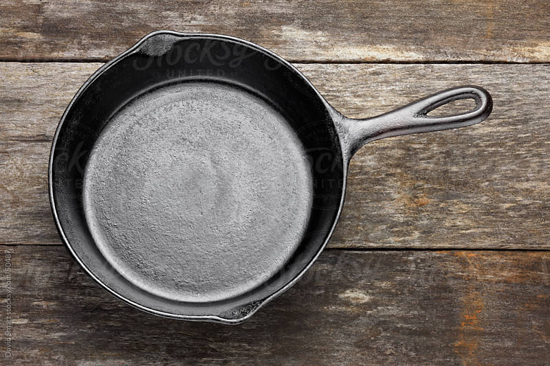 Empty cast iron skillet on weathered wood by David Smart for Stocksy United