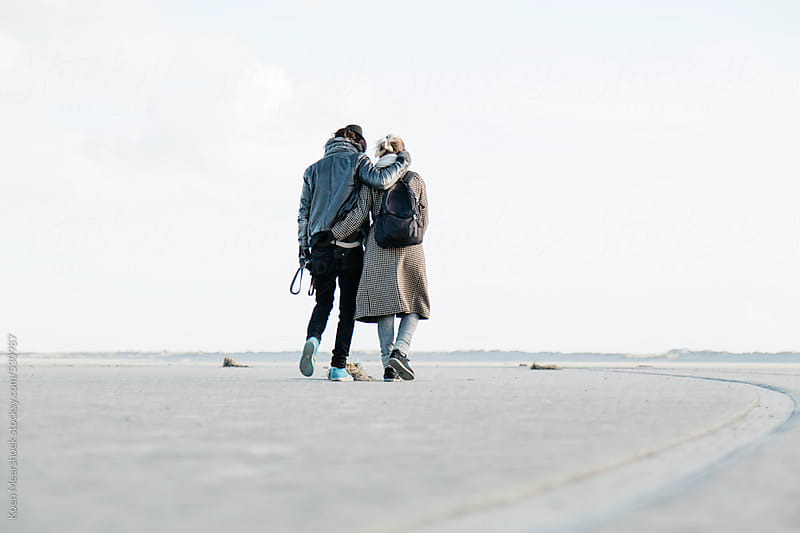 Young happy couple embraced while walking the dog. by Koen Meershoek for Stocksy United