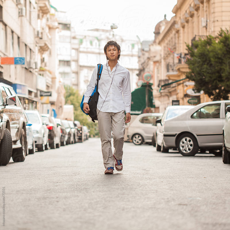 Young Asian Man Walking Down the Street by Mosuno for Stocksy United