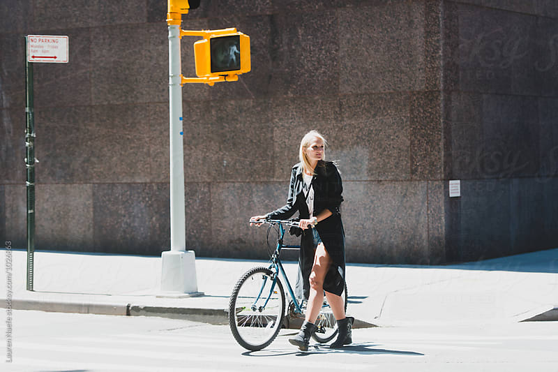 Young woman crossing street with bike by Lauren Naefe for Stocksy United