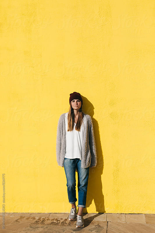 Portrait of a woman standing in front of a yellow wall. by BONNINSTUDIO for Stocksy United