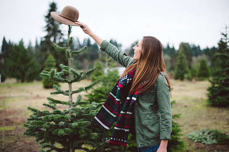 Young woman places hat on christmas tree by Kate Daigneault for Stocksy United