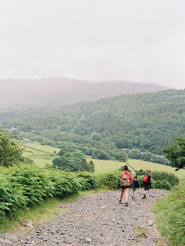 children walking down a mountainous path by Léa Jones for Stocksy United