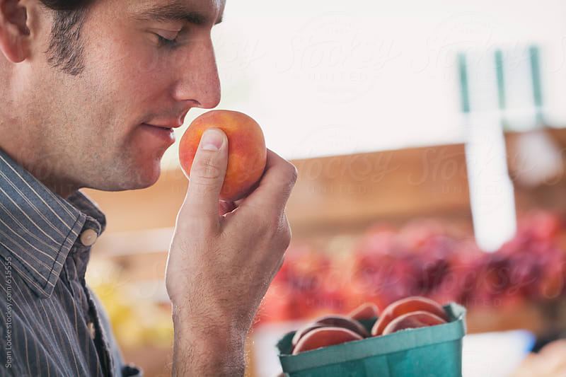 Market: Man Smelling Peaches Fresh From The Farm by Sean Locke for Stocksy United