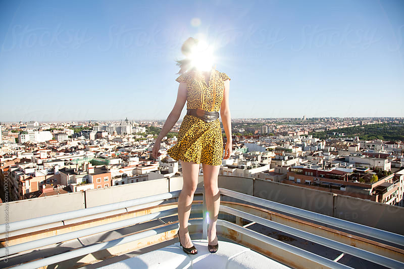 Woman reflecting light with a mirror in a rooftop terrace by Oscar Parasiego for Stocksy United