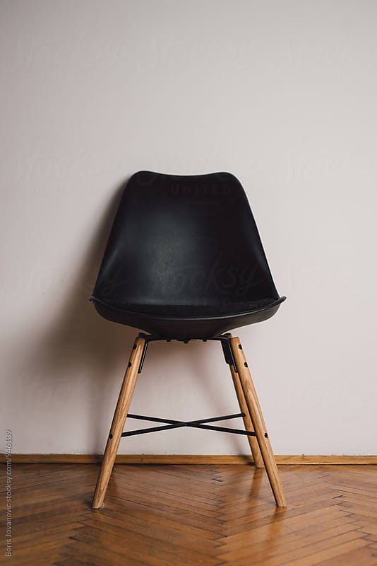 Black plastic chair against the white wall by Boris Jovanovic for Stocksy United