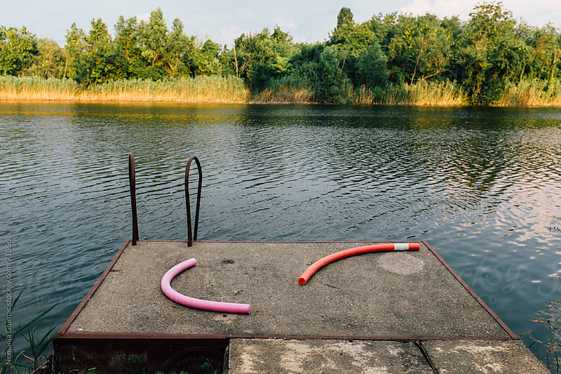 Concrete Dock With Two Swimming Noodles by Nemanja Glumac for Stocksy United