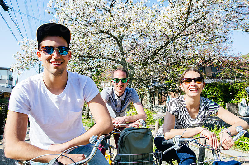 Portrait of happy friends on bicycle in spring. by BONNINSTUDIO for Stocksy United
