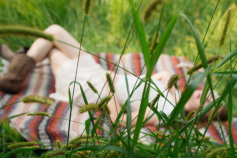 grass hides young woman laying on blanket by Tana Teel for Stocksy United