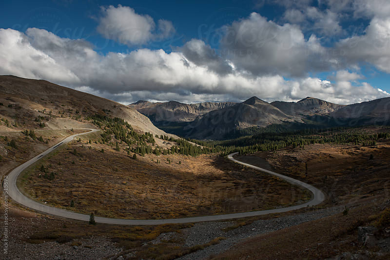 Curving road with mountains behind. by Mick Follari for Stocksy United