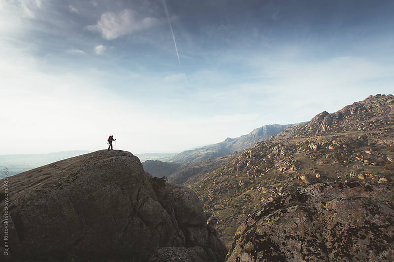 A silhuette of a person standing on a cliff wathing the view. by Dejan Ristovski for Stocksy United